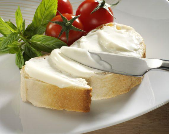 cream cheese on bread with tomato and mint